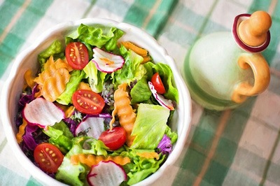 A white bowl full of healthy fresh salad ingredients on a checkered table cloth.