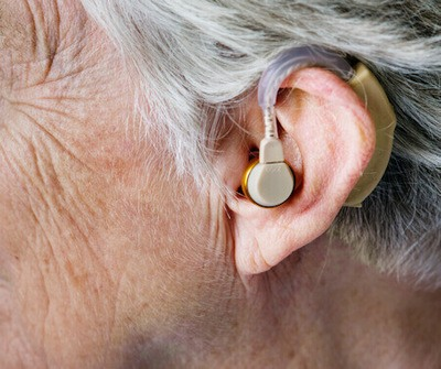 Close up photo of the left ear of a person wearing a beige colored hearing aid.