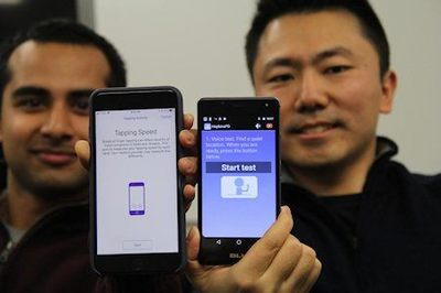 Johns Hopkins computer science students Srihari Mohan, left, and Andong Zahn, display the iPhone and Android smartphone apps they helped design to allow Parkinson's disease patients to measure the severity of their symptoms - Photo Credit: Noam Finkelstein/Johns Hopkins U.
