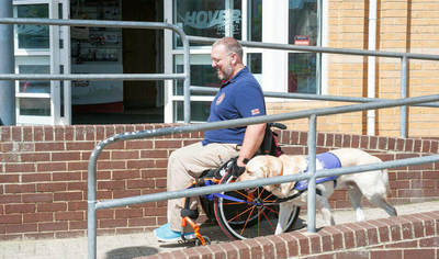 Outside a Hover Travel office a man in an orange wheelchair descends an access ramp with his service dog.