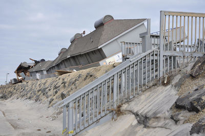 Hurricane aftermath photo showing eroded beach wall and tilted houses.