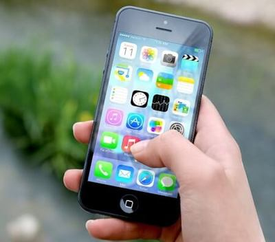 An Apple iPhone showing screen icons is being held in a persons hand