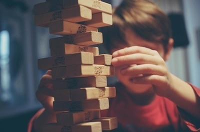 A child playing with a Jenga block tower.