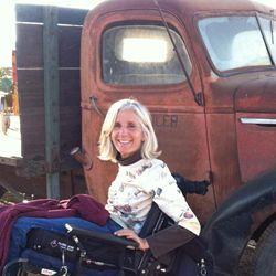 Jenny Weast in wheelchair alongside old truck