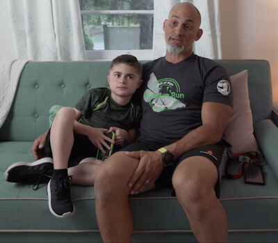 Jim Raffone and his son, Jamesy seated on a green couch.