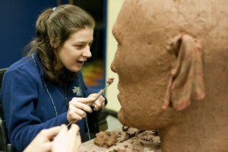 Volunteer Amanda Stahl smooths out the features of the Justin Dart puppet's face