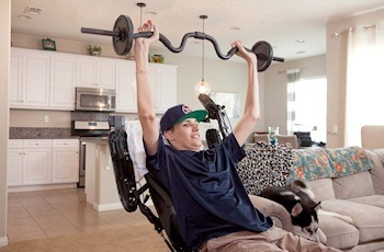 Kris Boesen of Bakersfield, California, is shown lifting weights. Boesen, who was paralyzed from the neck down following a car accident in March 2016, now has use of his arms and hands following treatment with AST-OPC1, an investigational stem cell treatment developed by Asterias Biotherapeutics.