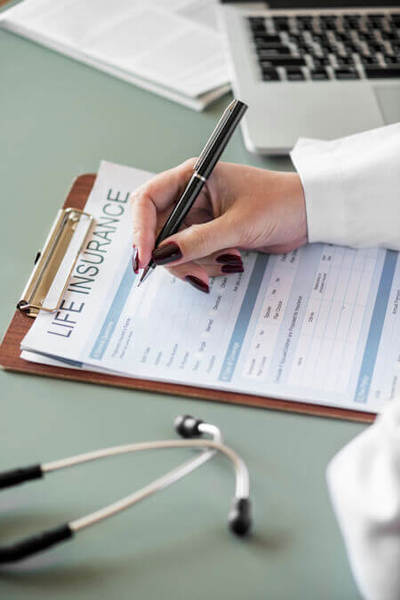 Photo shows a person filling out a life insurance form.
