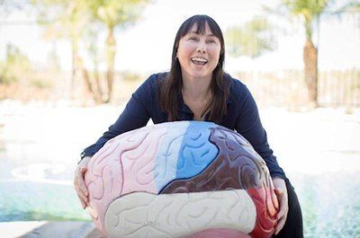 Dr. Lynette Louise (known affectionately as The Brain Broad) pictured with a large model of the human brain with colored segments.