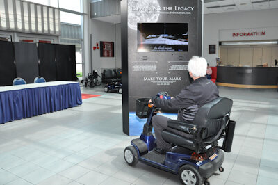 A People with Disabilities Program volunteer rides a motorized wheelchair around the lobby of the National Museum of the United States Air Force. Each volunteer chose a disability from an envelope upon entering the museum that specified the disability they would experience. This photo represents a disability that effects the participant's legs. (U.S. Air Force photo/Kimberly Gaither).