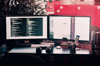 A two display computer with lines of code on one of the monitors, cellphone, keyboard and head phones in the foreground.