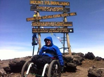 A happy Iain at Uhuru Peak on Mt Kilimanjaro in his Mountain Trike