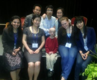 "University of Maryland Asst. Prof. Kan Cao (front row, center left) and her research team met with progeria patients like Devin Scullion (front row center), age 16, at the Progeria Research Foundation International Workshop in April 2013. The fatal genetic disorder causes children to age prematurely and die of heart attacks or strokes. ""It's a lot of motivation for us to work quickly,"" said Cao. Photo Credit: Courtesy of Kan Cao"