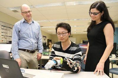 Michael Naish from Mechanical and Materials Engineering at Western and Ana Luisa Trejos from Electrical and Computer Engineering at Western examine a prototype of a wearable tremor suppression glove modeled by Western doctoral student Yue Zhou, who 3D-printed its key components - Photo Credit: Paul Mayne.