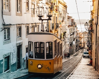 Yellow tram carriage suspended at the top of a narrow street with traditional architecture, Lisbon, Portugal.