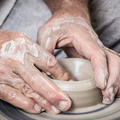 Close up image of two hands forming pottery on a potters wheel.