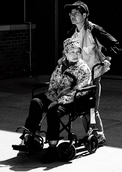 Black and white photograph of a man pushing an older woman in a wheelchair.