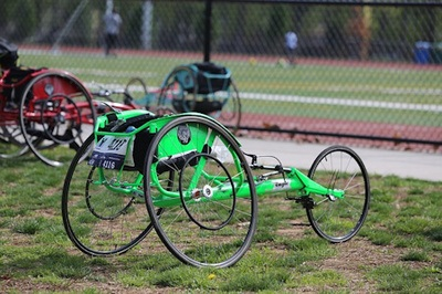 Photo of three racing wheelchairs colored green red, and blue.