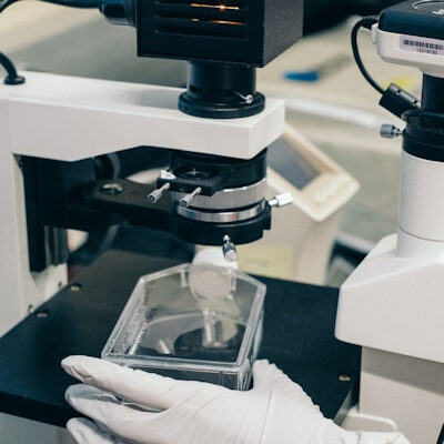 Medical researcher examining substance in clear dish under a microscope.