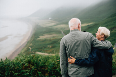 Older couple looking at each other at a location overlooking mountains and a beach.