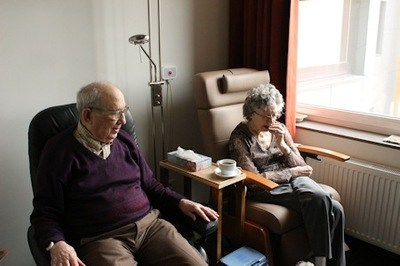 Elderly man and woman seated in chairs.