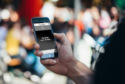Person using the RightHear app on a cellphone - The screen message is advising the user that - The toilets are in ten steps - Image Credit: RightHear - right-hear.com