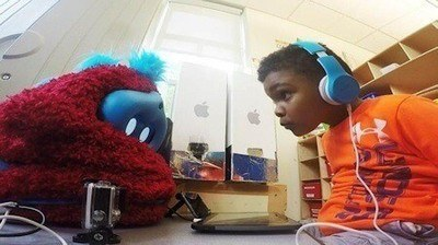 A pre-schooler interacts with a social robot companion. Photo Credit: Personal Robots group, M.I.T. Media lab