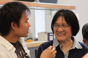 Rong Gan, right, listens as a biomechanics student discusses auditory research
