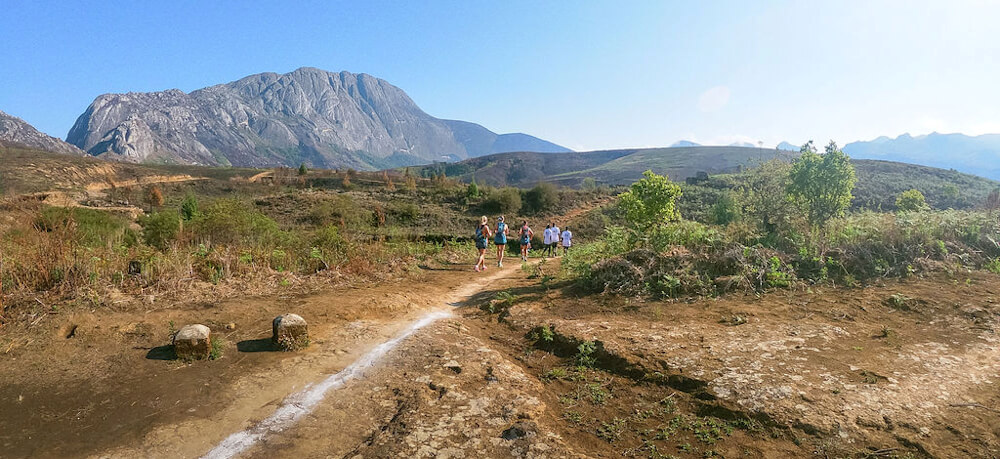 Running on the isolated trails of Mulanje Mountain in Southern Malawi - Six hikers on a trail leading over undulating terrain. Mulanje mountain can be seen at the top left of the picture.
