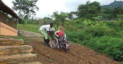 Sarah is helped up a hill on a dirt road by Cwmbale Nature Reserve wardens David Werikhe and Gabriel Alenyo.
