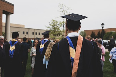 Students wearing academic gowns in school yard - Photo by Charles DeLoye on Unsplash.