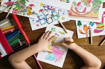 Image shows child coloring in a picture, colored pencils and completed colored pictures are scattered on the desk.