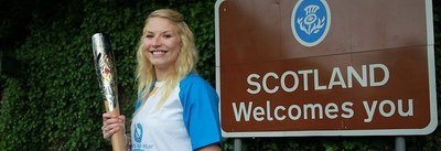 Sammi Kinghorn next to Scotland Welcomes You sign.