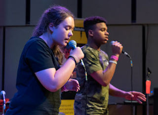 DaDaFest Scratch Performance photo of teen girl and boy singing into microphones.