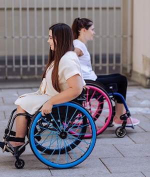 Example of Seksi Spokes featuring two wheelchairs. One wheelchair has pink spokes and rims, the other has blue spokes and rims.