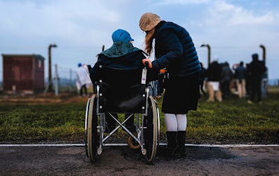 An elderly woman stands next to a person in a wheelchair near a green grassy field - Photo by Josh Appel on Unsplash.
