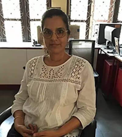 Seated photo of Shabnam Rangwala. She is pictured wearing glasses and a white top.