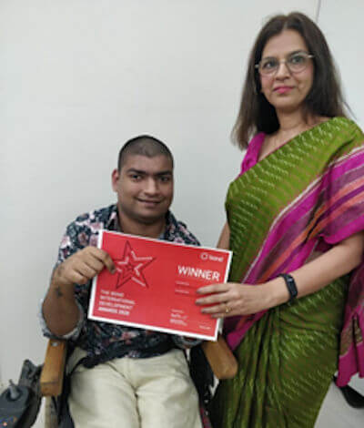 Shabnam Rangwala standing alongside a man in a wheelchair. They are both holding a red certificate.