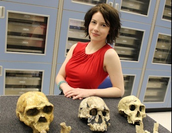 Image shows Shelby S. Putt standing next to a table with 3 ancient skulls on it. Photo Credit: University of Iowa.