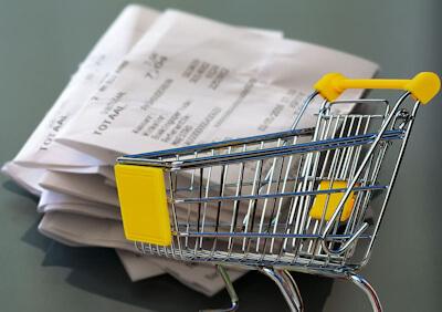 Miniature shopping cart in front of a cash register receipt.
