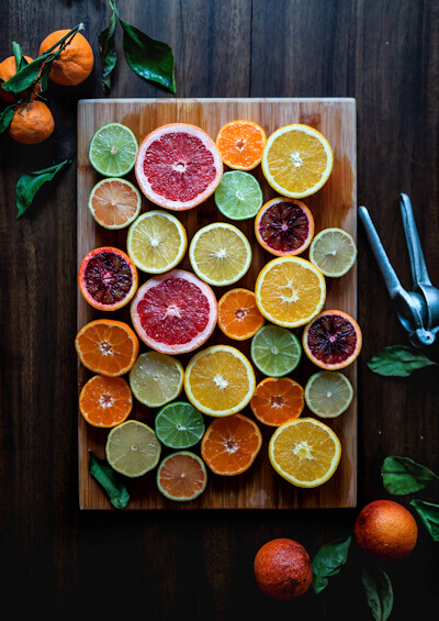 Picture of assorted sliced citrus fruits on a brown wooden chopping board - Photo by Edgar Castrejon on Unsplash.