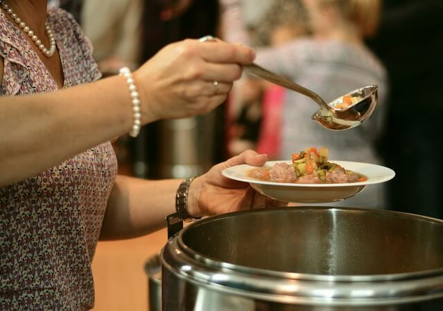 Woman ladles soup with her right hand from a pot into a bowl she holds with her left hand.