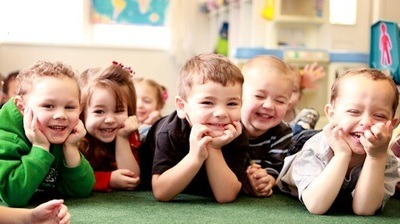 Laughing young children laying on the floor in a classroom.