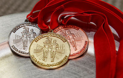 Gold, Silver and Bronze medals for the Summer 2018 N.H. Special Olympics rest on a display tray - (N.H. Air National Guard photo by Staff Sgt. Kayla White).