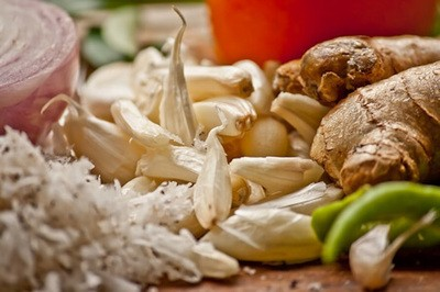 Close up image of age old favorite home remedy ingredients; garlic, ginger, onion, peppers, and herbs.