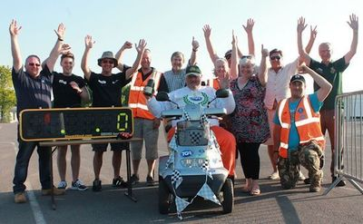 """Onboard his trusty TGA Breeze S4 GT, Steve Tarrant achieves a new 24-hour world record for: """"the greatest distance covered in 24 hours by a mobility scooter'.* Pictured celebrating on the finish line at Goodwood Motor Circuit with his pit crew that included engineers from TGA Mobility and Sales Science."""
