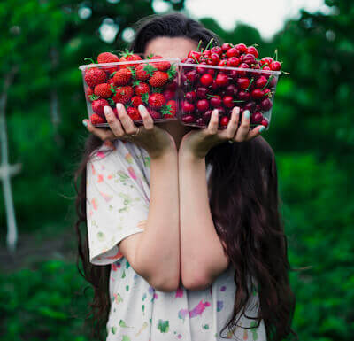Woman holding two containers of strawberries in front of her face - Photo by Elijah O'Donell on Unsplash.