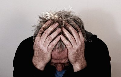 Head and shoulders shot of a stressed man holding his head in his hands.