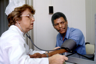 An adult African American male patient and a Caucasian female nurse wearing a lab coat. She is testing him for high blood pressure and they are both looking at the indication on the measuring instrument - Source:	National Cancer Institute - Creator:	Linda Bartlett (Photographer).