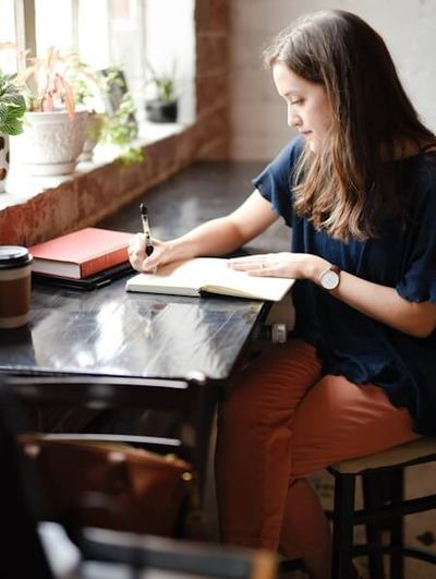 Teen girl sitting cross legged at a table writing in a journal.